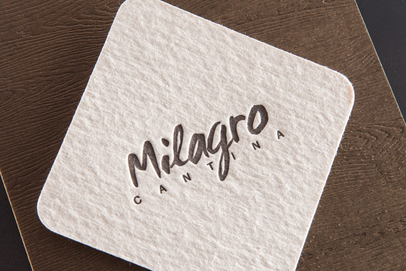 brown and white letterpress coaster